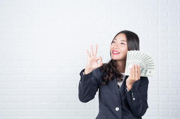 La mujer de negocios que sostenía el billete de banco, cobraba por separado, pared de ladrillo blanca hizo gestos con lenguaje de signos.