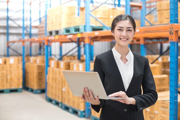 Mujer de negocios que sostiene la computadora portátil con la sonrisa en el almacén. personas que trabajan concepto.
