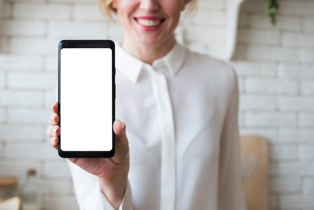 Mujer de negocios que sostiene smartphone con la pantalla en blanco