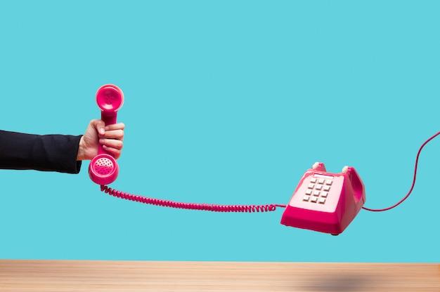 Mujer de negocios que sostiene el teléfono rojo