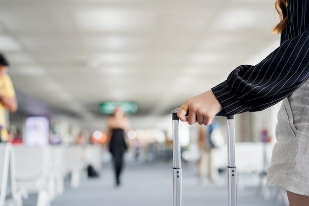 Mujer de negocios que toca el bolso de equipaje
