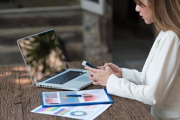 Mujer de negocios que trabaja en la computadora portátil buscando y mecanografiando en el smartphone, cierre para arriba.