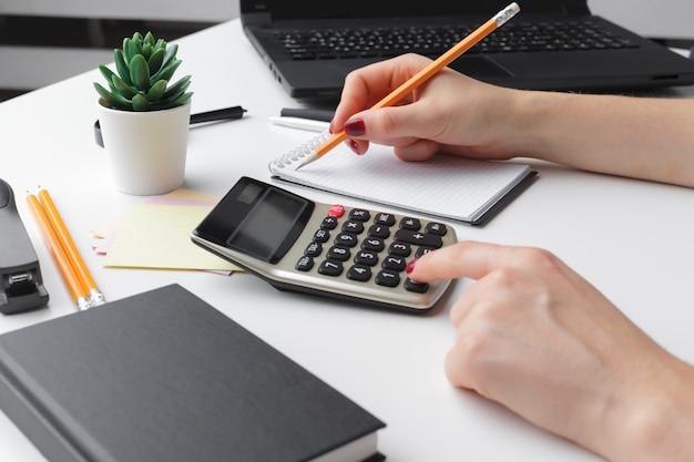 Mujer de negocios que trabaja con datos financieros mano usando calculadora