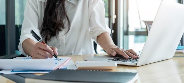 Mujer de negocios que trabaja en finanzas y contabilidad analizar el presupuesto financiero en casa, trabajar desde el concepto de casa