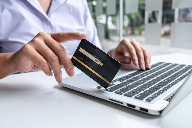 Mujer de negocios que usa la computadora portátil y que sostiene la tarjeta de crédito para pagar la página de detalles muestra la compra de compras en línea y el código de seguridad de entrada para ingresar la información de la tarjeta