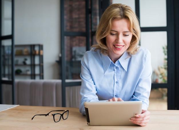 Mujer de negocios que usa la tableta en la mesa