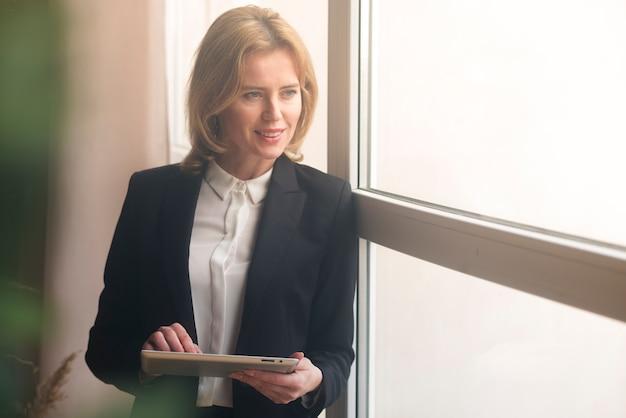 Mujer de negocios que usa la tableta en la ventana