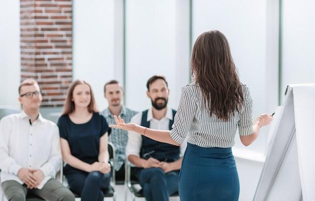 Mujer de negocios realizando un seminario para su equipo empresarial