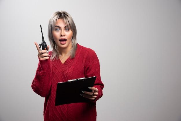 Mujer de negocios recibiendo una sacudida eléctrica sobre fondo gris.