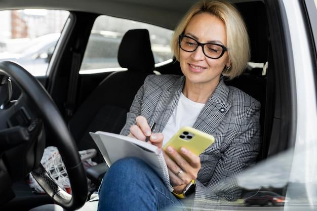 Mujer de negocios rubia comprobando su teléfono en su coche