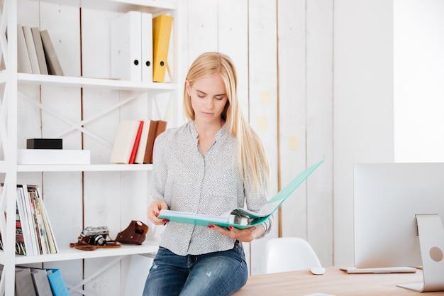 Mujer de negocios rubia concentrada sentada en su lugar de trabajo y mirando a través de documentos