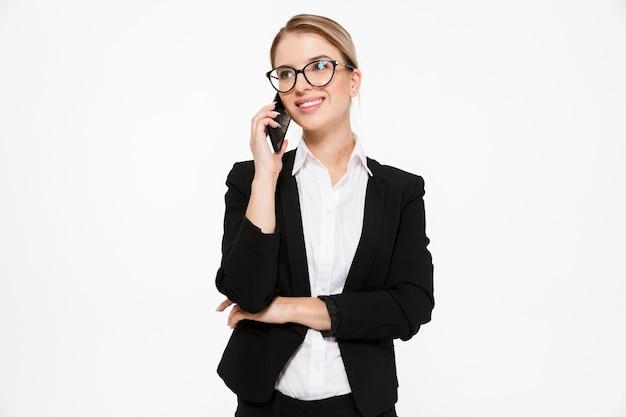 Mujer de negocios rubia contenta en anteojos hablando por teléfono y mirando a otro lado sobre blanco