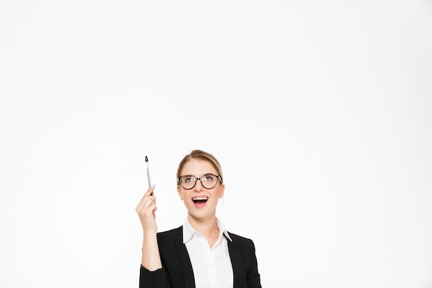 Mujer de negocios rubia feliz en anteojos apuntando y mirando hacia arriba sobre la pared blanca