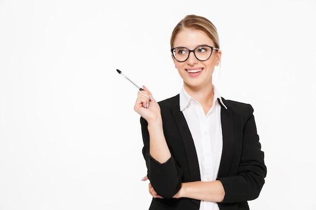 Mujer de negocios rubia feliz en anteojos con bolígrafo en mano teniendo idea y mirando a otro lado sobre la pared blanca