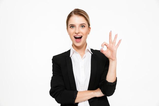Mujer de negocios rubia feliz mostrando signo bien y con la boca abierta sobre blanco