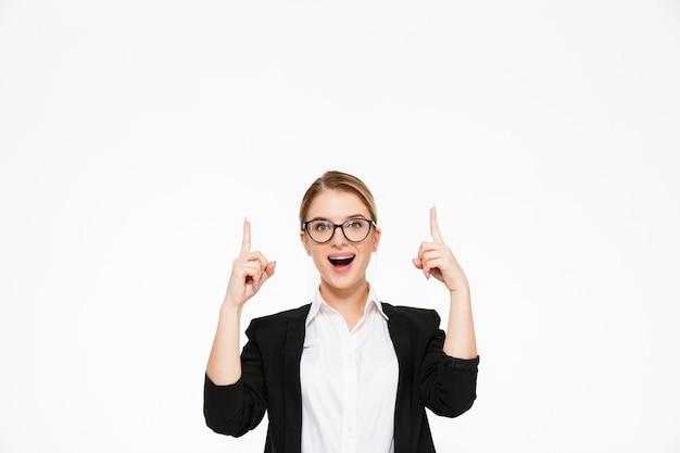 Mujer de negocios rubia feliz sorprendida en anteojos apuntando hacia arriba