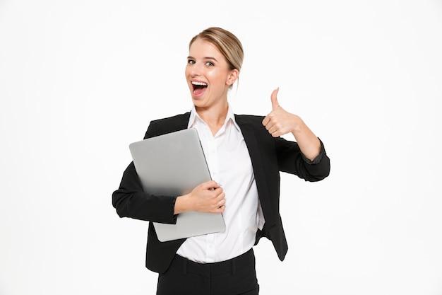 Mujer de negocios rubia feliz sosteniendo la computadora portátil y mostrando el pulgar hacia arriba mientras que sobre la pared blanca