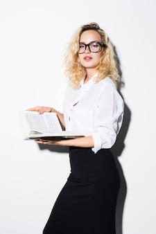 Mujer de negocios rubia feliz sosteniendo un libro aislado en la pared blanca