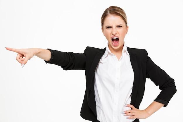 Mujer de negocios rubia gritando enojado sosteniendo el brazo en la cadera y apuntando lejos sobre blanco