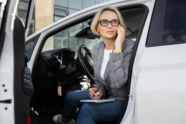 Mujer de negocios rubia hablando por su teléfono en su coche