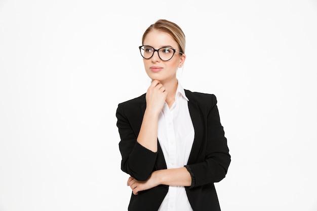 Mujer de negocios rubia joven atractiva en anteojos de la mano cerca de la barbilla y mirando a otro lado sobre blanco