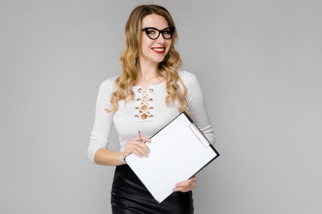 Mujer de negocios rubia joven atractiva en ropa blanco y negro sonriendo mostrando portapapeles en sus manos de pie en la oficina en gris