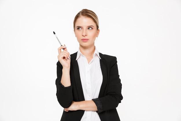 Mujer de negocios rubia pensativa que sostiene la pluma y que mira lejos sobre la pared blanca