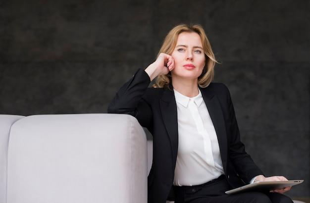 Mujer de negocios rubia pensativa con la tableta