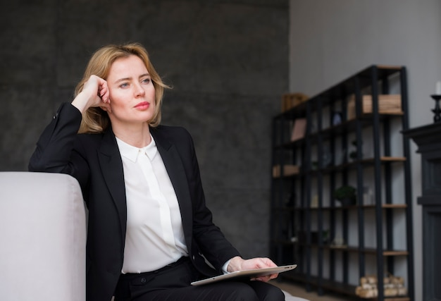 Mujer de negocios rubia pensativa en traje con la tableta