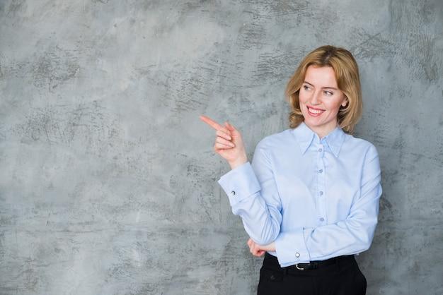 Mujer de negocios rubia que señala el dedo lejos