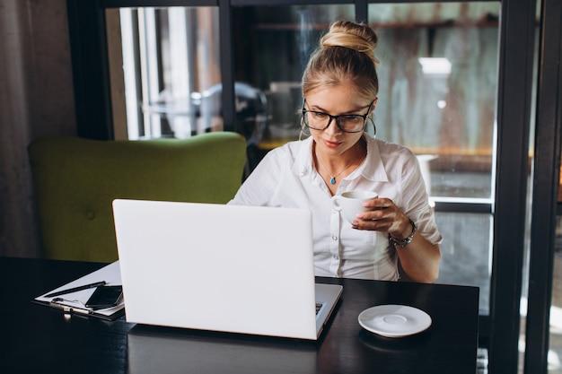 Mujer de negocios rubia que se sienta en espacio de trabajo y que usa el ordenador portátil en la oficina, ella mira una carpeta con los documentos, hablando por teléfono y bebiendo una taza de café.