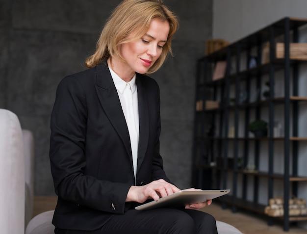 Mujer de negocios rubia que sienta y que usa la tableta