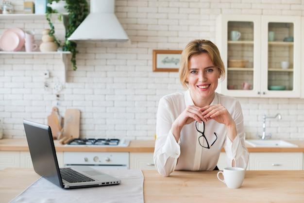 Mujer de negocios rubia que se sienta con la taza de café y el ordenador portátil