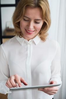 Mujer de negocios rubia que usa la tableta