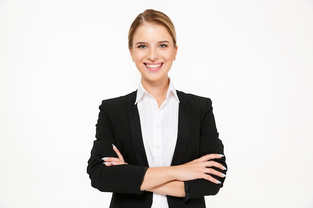 Mujer de negocios rubia sonriente que presenta con los brazos cruzados