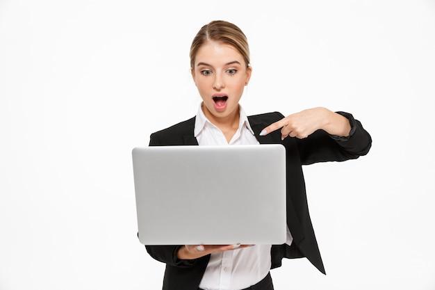 Mujer de negocios rubia sorprendida que sostiene la computadora portátil y que lo señala sobre la pared blanca
