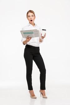 Mujer de negocios rubia sorprendida sosteniendo el periódico y una taza de café mientras sobre la pared blanca