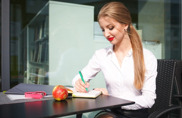 Mujer de negocios con una sartén en la mano escribe en un cuaderno