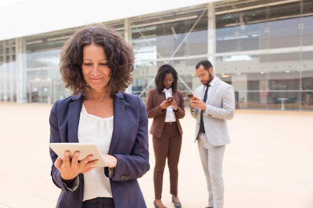 Mujer de negocios satisfecha feliz que usa la tableta afuera