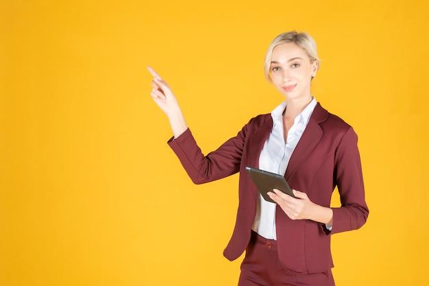 La mujer de negocios está señalando algo en fondo amarillo