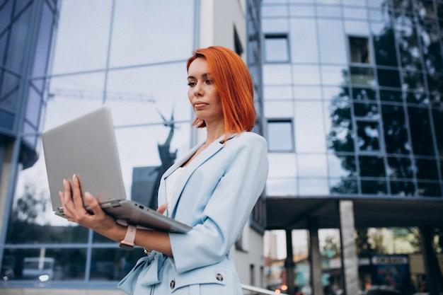 Mujer de negocios senior con laptop por centro de oficina