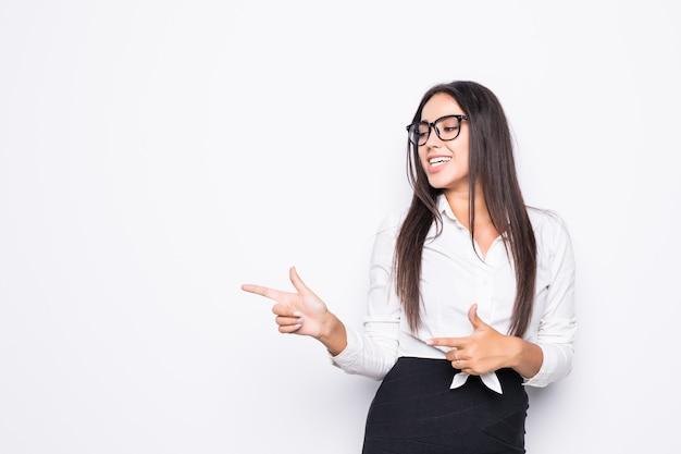 Mujer de negocios sentada en el escritorio mirando a un lado y apuntando con el dedo al espacio vacío de la copia en blanco