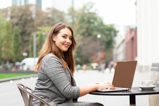 Mujer de negocios sentado en una cafetería en la calle, trabajando en un ordenador portátil.