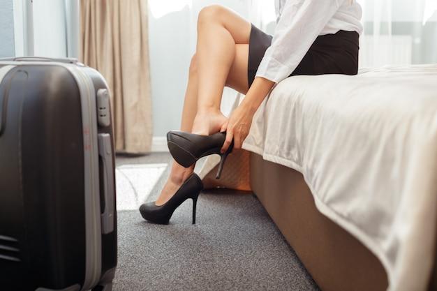 Mujer de negocios sentado en la cama en la habitación del hotel