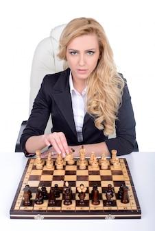 Mujer de negocios sentado delante de ajedrez y planificación.