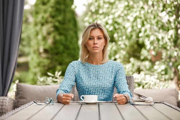 Mujer de negocios está sentado en tensión con café en una mesa en una terraza de verano. copyspace, verde.