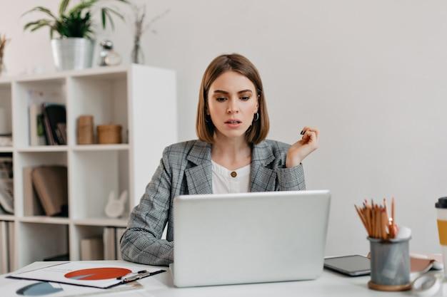 Mujer de negocios seria con ansiedad se ve en la computadora portátil. retrato de niña con corte de pelo corto en oficina blanca.