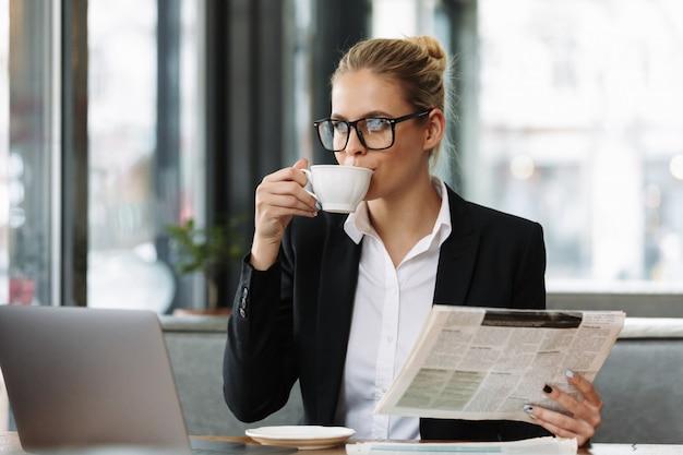 Mujer de negocios seria leyendo el periódico.
