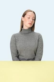 Mujer de negocios seria sentada a la mesa sobre un fondo rosa de estudio. el retrato en estilo minimalista