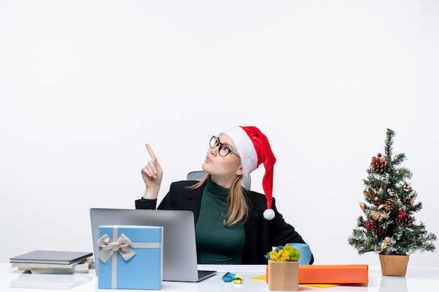 Mujer de negocios seria sorprendida con sombrero de santa claus sentado en una mesa con un árbol de navidad y un regalo apuntando arriba sobre fondo blanco.